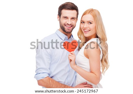 Celebrating their love. Beautiful young loving couple bonding to each other and holding heart shape paper while standing isolated on white background  - stock photo