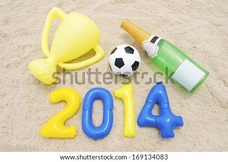 Celebrating 2014 with soccer ball football, inflatable trophy, and champagne bottle - stock photo