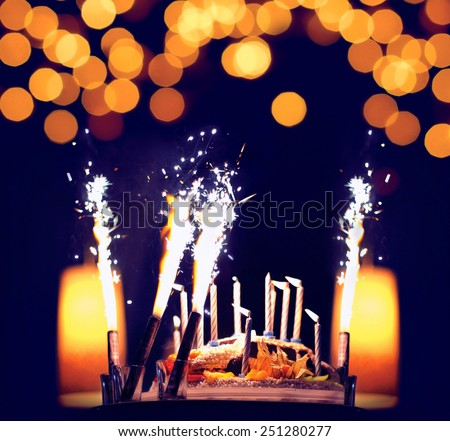 Celebration, birthday cake with candles, bright lights bokeh - stock photo