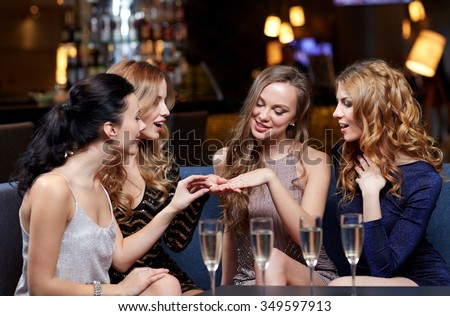celebration, friends, bachelorette party and holidays concept - happy woman showing engagement ring to her friends with champagne glasses at night club - stock photo
