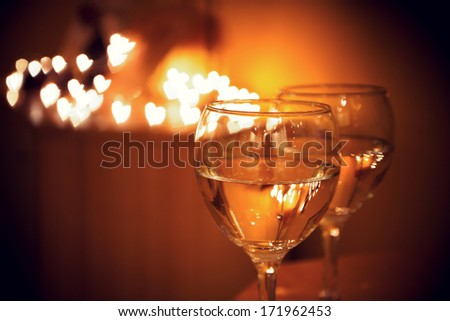 Celebration.Glasses of wine. The concept of Valentine's Day. Bokeh in the background of glasses are shaped like heart. - stock photo