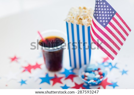celebration, patriotism and holidays concept - close up of american flag, coca cola cup, popcorn and candies with stars confetti decoration at 4th july party on independence day - stock photo
