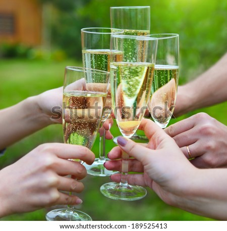 Celebration. People holding glasses of champagne making a toast outdoors - stock photo