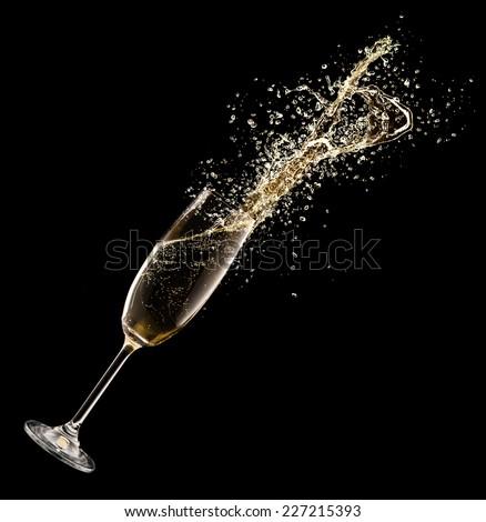 Celebration theme. Glass of champagne with splash, isolated on black background - stock photo