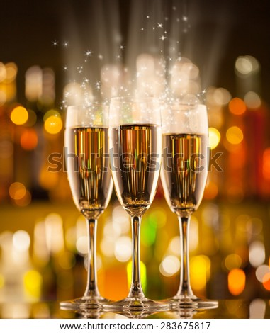 Celebration theme with three glasses of champagne. Blur bottles on background - stock photo