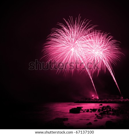 Celebration with colorful fireworks over the sea near a marina - stock photo