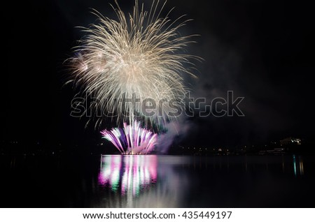 Celebration with colorful fireworks show with rockets bursting above the lake - stock photo