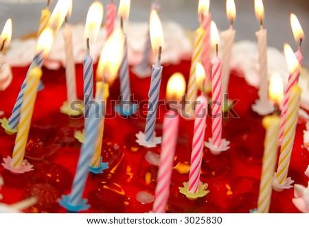 Celebratory cake and burning candles (shallow dof) - stock photo