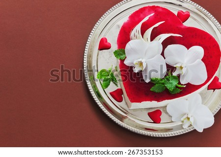 celebratory cake in the form of heart with orchid flowers on a brown background. valentine's day, mother's day. copy space background - stock photo