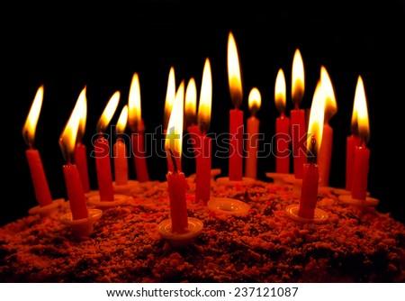 Celebratory cake with burning candles on a dark background - stock photo