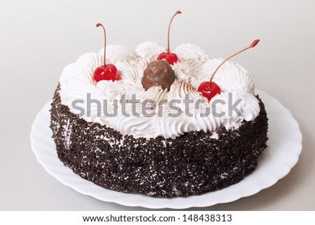 Celebratory chocolate cake with cherries and cream - stock photo
