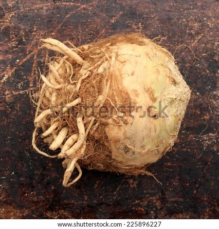 Celeriac on brown rustic background - stock photo