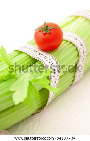 Celery and tomato with tape measure on the white background, concept of healthy lifestyle and diet - stock photo