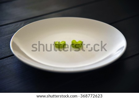 Celery Hearts on a White Plate on a Black Kitchen Woody table  - stock photo