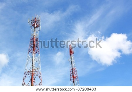 Cell phone and communication towers against blue sky with scattered clouds - stock photo