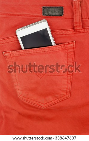 Cell phone in back pocket of red jeans - stock photo