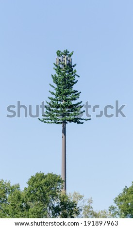 Cell phone tower trying to hide as a fir tree - stock photo
