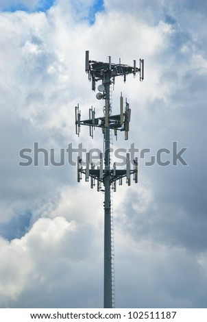 Cell tower and radio against a dark, cloudy sky - stock photo