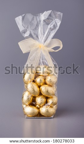 Cellophane bag of gold coloured chocolate mini easter eggs, with a bow round the top of the bag, on a grey background. - stock photo