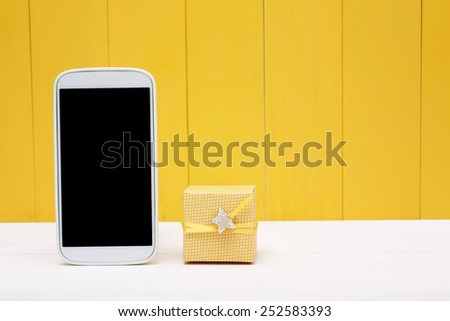 Cellphone and small gift box over yellow wooden wall - stock photo
