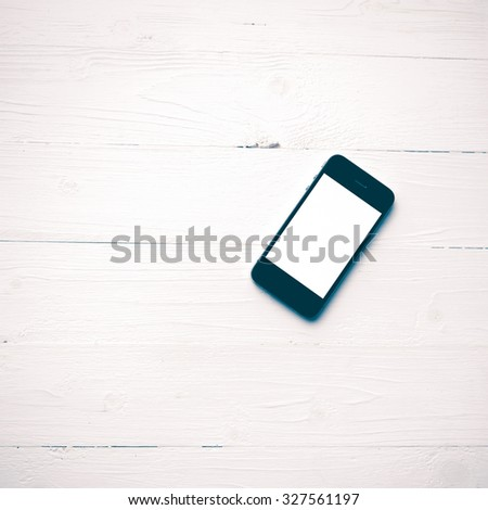 cellphone over white table vintage style - stock photo