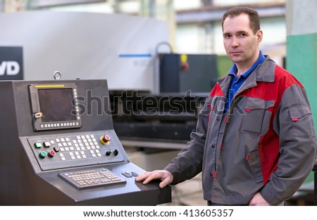 Cellular Manufacturing: Industrial Man Technician Worker at Computerized CNC Punch Press Machine in Factory Workshop - stock photo