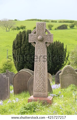 Celtic Cross Against Green Fields and Stormy Skies, England. - stock photo