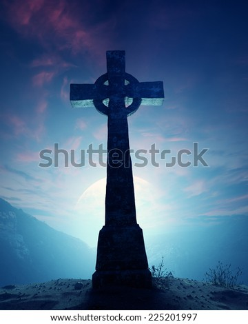 Celtic Cross with moonscape on crest of rocky mountain - stock photo