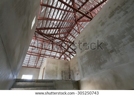 cement concrete wall and roof with steel beam and silver foil insulation in residential building construction site - stock photo
