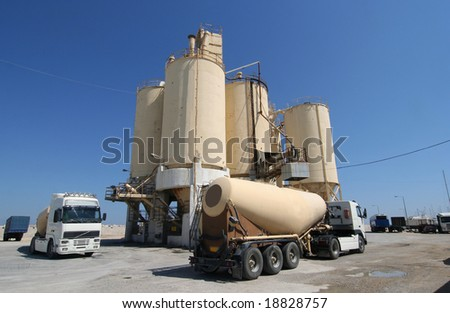 Cement factory with silos and trucks - stock photo