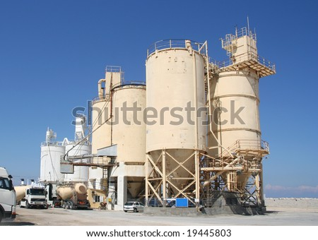 Cement industry with silos and trucks - stock photo