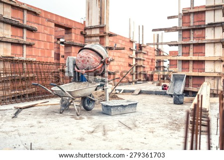 Cement mixer machine at construction site, tools, wheelbarrow, sand and bricks at new house building. - stock photo