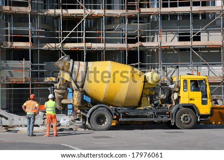 Cement mixer truck parked in front of a new building under construction with scaffolding. - stock photo