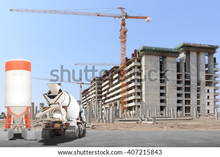 Cement mixer truck with precast concrete piles at building under construction - stock photo