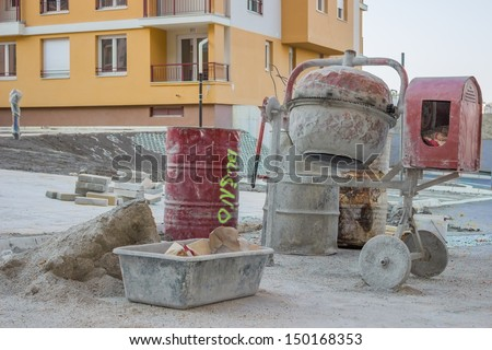 Cement mixer with barrel and plastic cement mixing trough at a building site  - stock photo