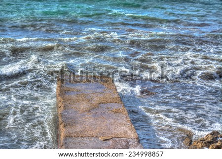 cement pier surrounded by waves. Shot in Alghero, Italy - stock photo