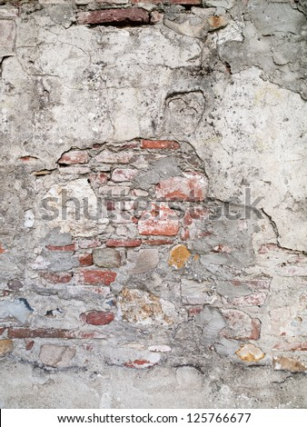Cement plastering with red brick showing through this ancient wall. - stock photo