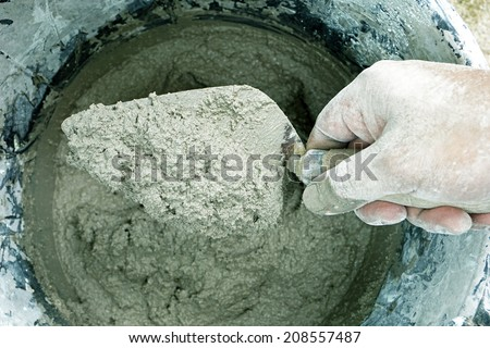 cement portland gray fresh mortar mix with spatula tool in bucket - stock photo