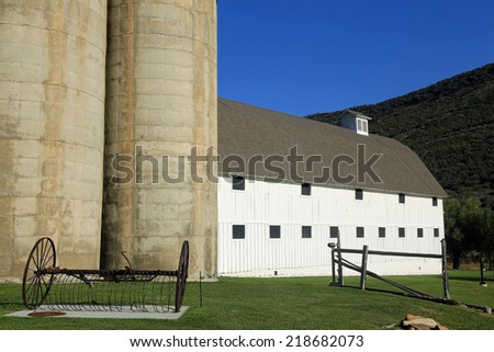 Cement silos and a white barn on a farm, Utah, USA. - stock photo