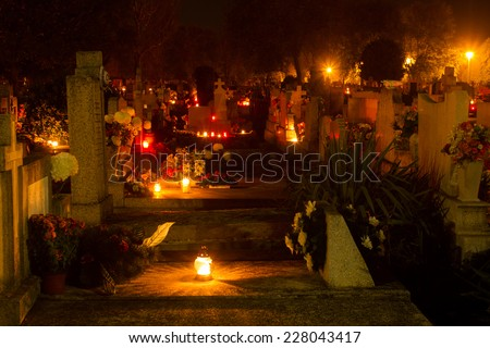 cemetery decorated with candles for All Saints Day at night - stock photo