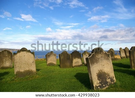 Cemetery in Whitby, North Yorkshire, United Kingdom. Cloudy autumn day. Crisp weather at seaside. Old graves and tombstones. - stock photo