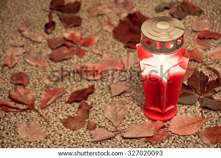 cemetery red lantern candle with autumn leaves  (selective focus) - stock photo