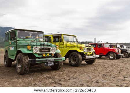 CEMORO LAVANG, JAVA, INDONESIA - JANUARY 27, 2012: Colorful off-road cars ready for tourist trip to Semeru volcano against cloudy sky  - stock photo