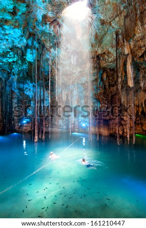 Cenote Dzitnup near Valladolid, Mexico. Couple (blured) swiming in lovely cenote with turquoise waters and large stalactites - stock photo