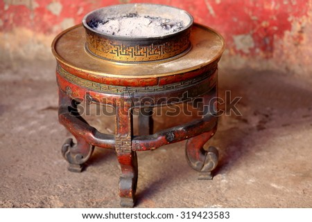 Censer full of ashes on brass topped carved wooden round table in the Tashilhunpo-Heap of Glory monastery seat of Panchen Lama. Shigatse city.at the Yarlung Tsangpo and Nyang Chu rivers junction-Tibet - stock photo