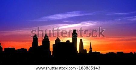 Center City Philadelphia scenic skyline cityscape silhouette with skyscraper buildings and historic landmarks with spectacular color sunset afterglow over colorful blue to orange sky - stock photo