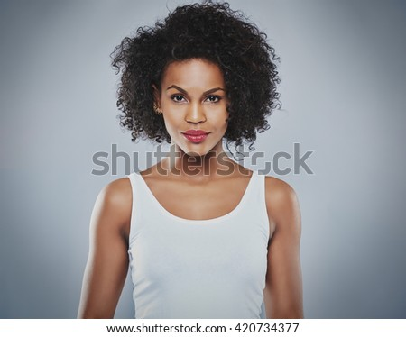 Centered front view of single pretty grinning woman wearing white sleeveless undershirt and calm expression over gray background - stock photo