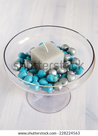Centerpiece with candle and light blue stones - stock photo