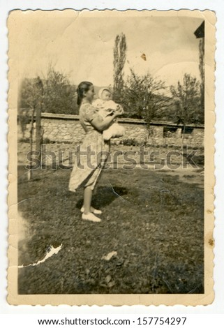 CENTRAL BULGARIA, BULGARIA - CIRCA 1955: the area Plovdiv - A woman in a garden holding an unidentified baby in her arms - Note: quite blurriness, better at smaller sizes - circa 1955 - stock photo