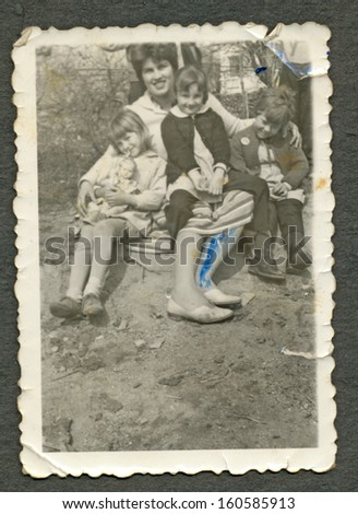 CENTRAL BULGARIA, BULGARIA - CIRCA 1955: Woman with her three children sitting on the ground  circa 1955 - stock photo